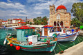 Colorful Greek fishing boats moored in the port of Aegina island, near a traditional small Greek church