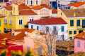 Colorful buildings with red tile roofs and pigeons on them in Plaka area, Athens