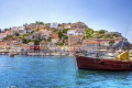 Fishing boat backdropped by the traditional colorful buildings, Hydra island