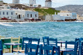 Seaside tavern with blue chairs and the famous windmills, Mykonos island