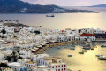 Mykonos island port during susnet, golden sea and white houses