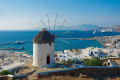 Windmill and chora backdropped by the waters of the Mediterranean, Mykonos island