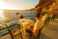 Tavern by the sea at Ammoudi Bay port at sunset, Santorini island