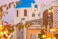 Romantic picturesque alley in Oia town at dusk, Santorini island