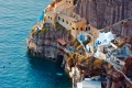 Houses perched on the volcanic cliffs by the sea in Oia town, Santorini island
