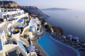 View of sugar cubed houses, pool and the infinite blue sea encircling the caldera, Santorini island