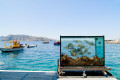Aquarium backdropped by the turquoise waters of the port, Santorini island