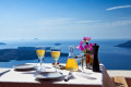 Table with wine backdropped by the caldera and the blue sea, Santorini island