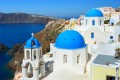 Blue church domes perched on the volcanic caldera cliffs backdropped by the Aegean Sea, Santorini island