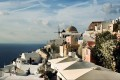 Unique view of sugar cubed houses and an old windmill backdropped by the vivid blue Aegean Sea, Santorini island