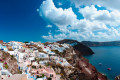 Panoramic view of candy colored houses perched on the volcanic caldera cliffs, Santorini island