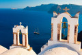 Church bell towers backdropped by the vast blue sea and a sailing ship, Santorini island
