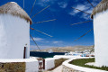 Looking through the old traditional windmills down to Mykonos island chora