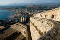 The imposing walls of castle Palamidi, in background the bay and the village of Nafplion city, Greece