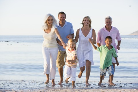 Photo of a big happy family walking on the beach