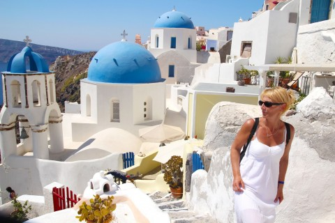 Tourist wandering at the white-washed alleys of Santorini island, Greece