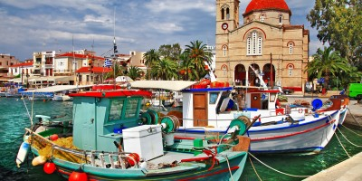 Idyllic Greek island port with colorful boats and a church, Aegina island