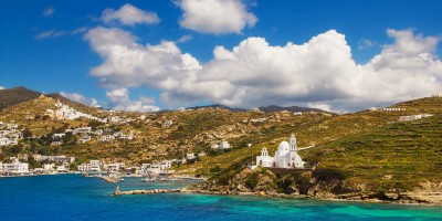 The port, exotic coastline and a white washed traditional Orthodox church on Ios island