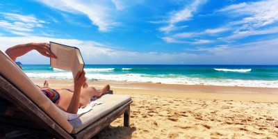 Woman relaxing and reading a book by the sea