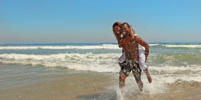 Happy couple splashing by the sea