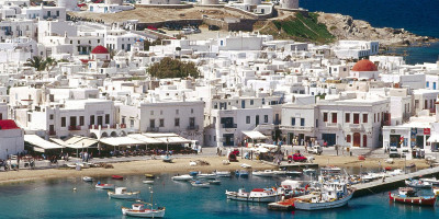 Overview of white washed houses, the famous old windmills and the turquoise Aegean sea encircling Mykonos island