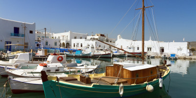 Traditional Greek boats and white houses at Parikia port, Paros island