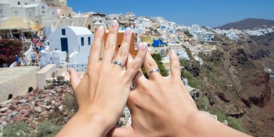 Hands of newlyweds on romantic honeymoon, Santorini island