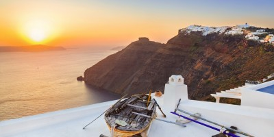 Panoramic view of sugar cubed houses perched on the volcanic cliffs of the caldera at sunset, Santorini island