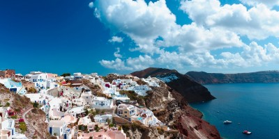 Panoramic view of sugar cubed houses perched on the volcanic cliffs of the caldera, Santorini island