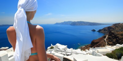 Woman enjoying the view of the caldera, the white houses and the infinite blue sea, Santorini island