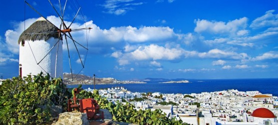 Old stone windmill backdropped by white washed houses, Mykonos island