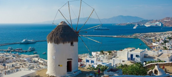 Old stone windmill backdropped by traditional buildings, Mykonos island