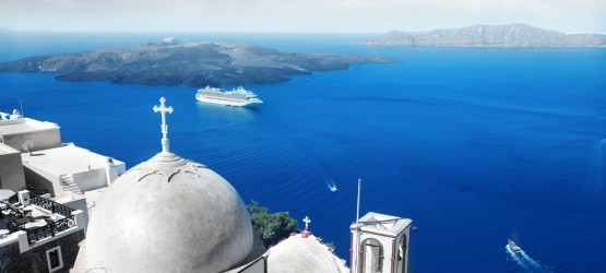 View of church dome and the vivid blue Aegean Sea encircling the volcanic caldera, Santorini island