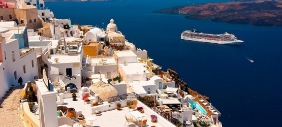 View of candy colored houses perched on the volcanic cliffs of the caldera, Santorini island