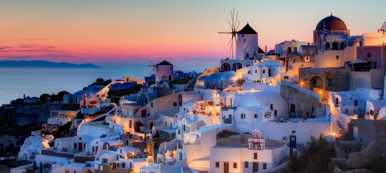 Traditional houses and windmill by night, Santorini island sunset